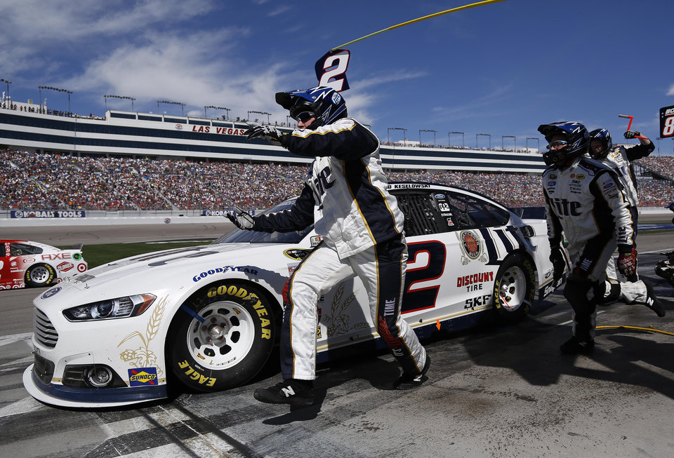 Photo - Brad Keselowski pulls out of pit row as his pit crew members finish changing his tires during a NASCAR Sprint Cup Series auto race on Sunday, March 9, 2014, in Las Vegas. Keselowski won the race. (AP Photo/Julie Jacobson)