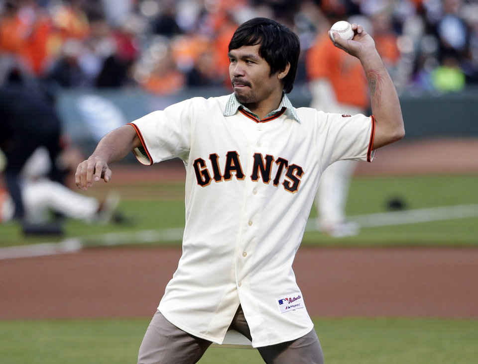 Photo - Boxer Manny Pacquiao throws a ceremonial first pitch before a baseball game between the San Francisco Giants and the Milwaukee Brewers, Friday, Aug. 29, 2014, in San Francisco. (AP Photo/Marcio Jose Sanchez)