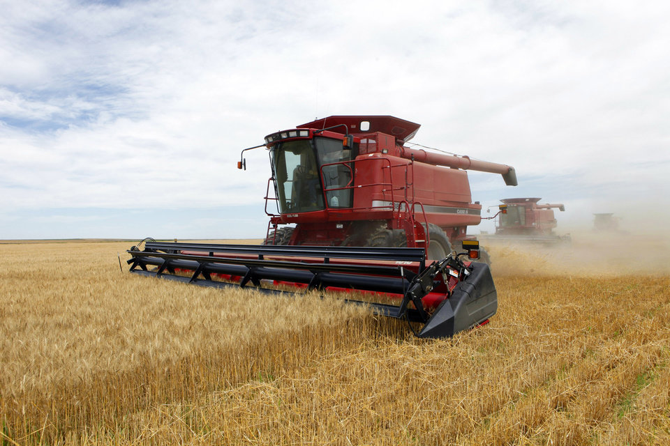 Photo - FILE - In this July 9, 2009 file photo three combines harvest the winter wheat on the Cooksey farm near Roggen, Colo. Farm-state lawmakers are pushing for final passage of the massive, five-year farm bill as it heads to the House floor Wednesday — member by member, vote by vote. There are goodies scattered through the bill for members from all regions of the country: a boost in money for crop insurance popular in the Midwest; higher cotton and rice subsidies for Southern farmers; renewal of federal land payments for Western states. There are cuts to the food stamp program — $800 million a year, or around 1 percent — for Republicans who say the program is spending too much money, but they are low enough that some Democrats will support them.  (AP Photo/Ed Andrieski, File)