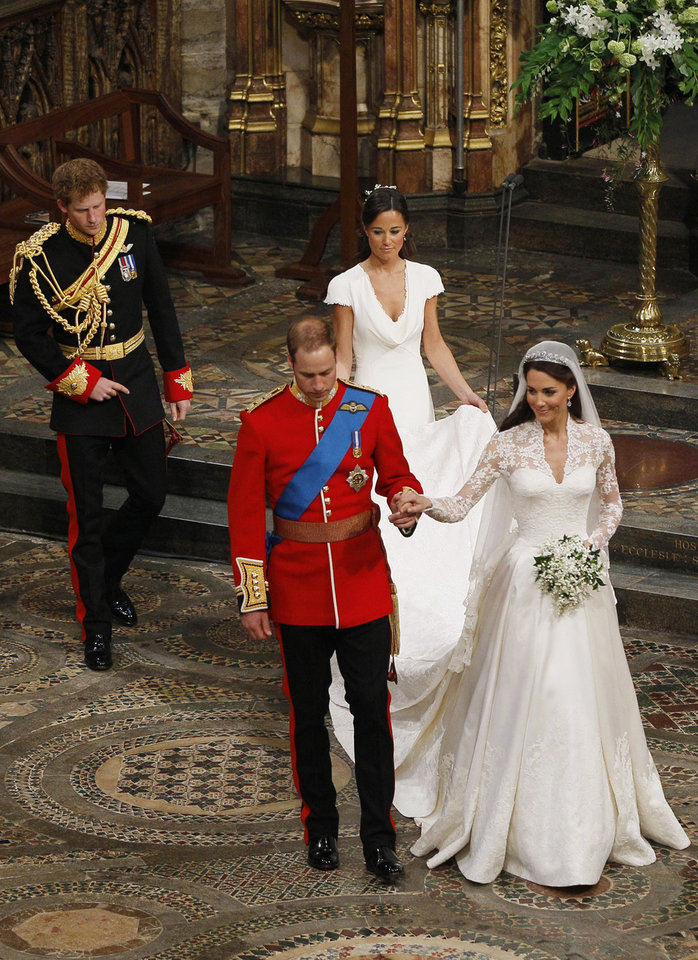 Photo - Britain's Prince William, foreground left, and his wife Kate, the Duchess of Cambridge, foreground right, walk hand in hand as Britain's Prince Harry, William's best man, back left, and maid of honour Philippa Middleton, back right, accompany them following their wedding service at Westminster Abbey in London, Friday, April 29, 2011. (AP Photo/Kirsty Wigglesworth, Pool)