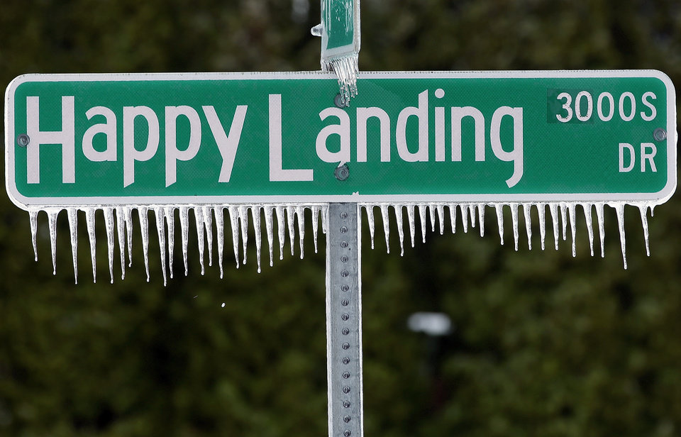 Photo - Icicles hang from a street sign after a fast moving snow storm blanketed central Illinois, Friday, Feb. 22, 2013, in Springfield, Ill. Powerful wind gusts created large snow drifts on many roadways, making navigating the slick conditions a challenge. Accidents and slide-offs were reported from Kansas to Michigan as the storm pushed east. (AP Photo/Seth Perlman)