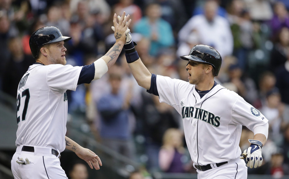 Photo - Seattle Mariners' Justin Smoak, right, is congratulated by Corey Hart as he crosses home on his two-run home run against the Kansas City Royals in the fourth inning of a baseball game Saturday, May 10, 2014, in Seattle. (AP Photo/Elaine Thompson)