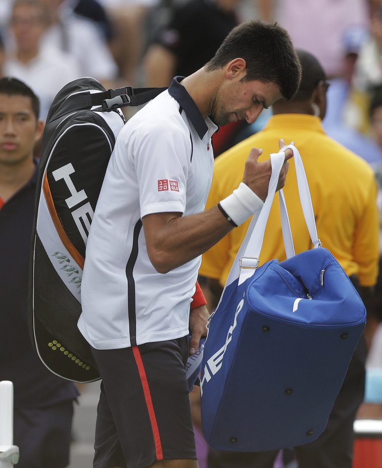 Photo -   Serbia's Novak Djokovic walks off the court after the semifinal match against Spain's David Ferrer was postponed because of approaching inclement weather at the 2012 US Open tennis tournament, Saturday, Sept. 8, 2012, in New York. (AP Photo/Mike Groll)