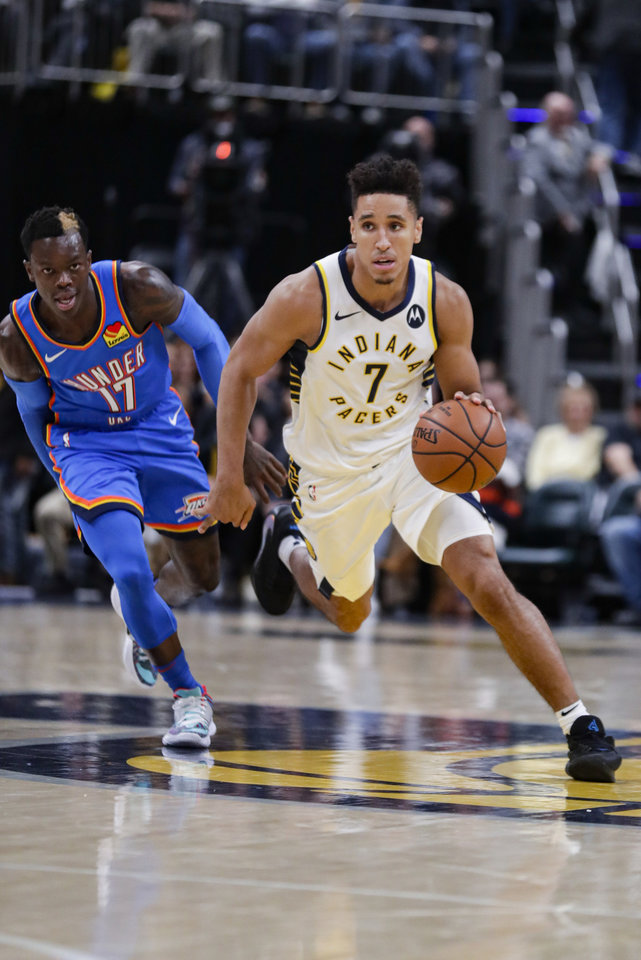 Photo - Indiana Pacers guard Malcolm Brogdon (7) drives on Oklahoma City Thunder guard Dennis Schroeder (17) during the second half of an NBA basketball game in Indianapolis, Tuesday, Nov. 12, 2019. The Pacers won 111-85. (AP Photo/Michael Conroy)