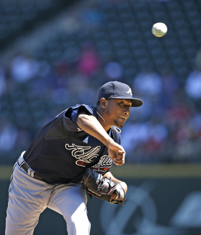 Photo - Atlanta Braves starting pitcher Julio Teheran throws against the Seattle Mariners in the first inning of a baseball game Wednesday, Aug. 6, 2014, in Seattle. (AP Photo/Elaine Thompson)