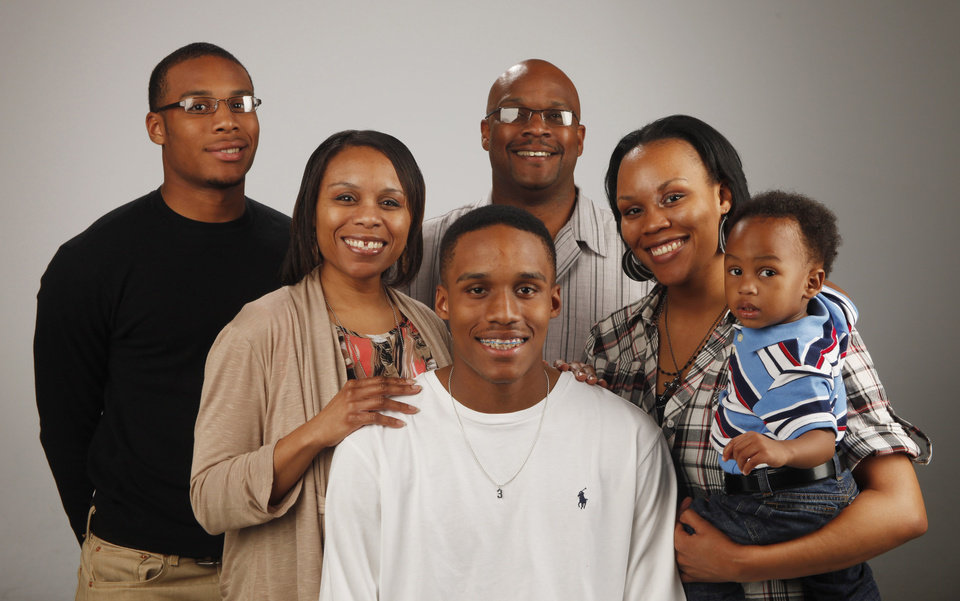Photo - Big All-City basketball player of the year James Woodard of Edmond Memorial with his family behind him, from left, brother Jordan Woodard, mom Petra Woodard, dad Marcus Woodard, sister Jasmyne Walker and his nephew Zavier Walker, 17 months, at OPUBCO studio, Tuesday April 3, 2012. Photo by Doug Hoke, The Oklahoman