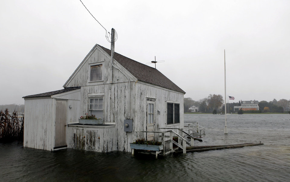 Photo -   A house is inundated by flood water as Hurricane Sandy approaches, Monday, Oct. 29, 2012, in Center Moriches, N.Y. Hurricane Sandy continued on its path Monday, as the storm forced the shutdown of mass transit, schools and financial markets, sending coastal residents fleeing, and threatening a dangerous mix of high winds and soaking rain.  (AP Photo/Jason DeCrow)