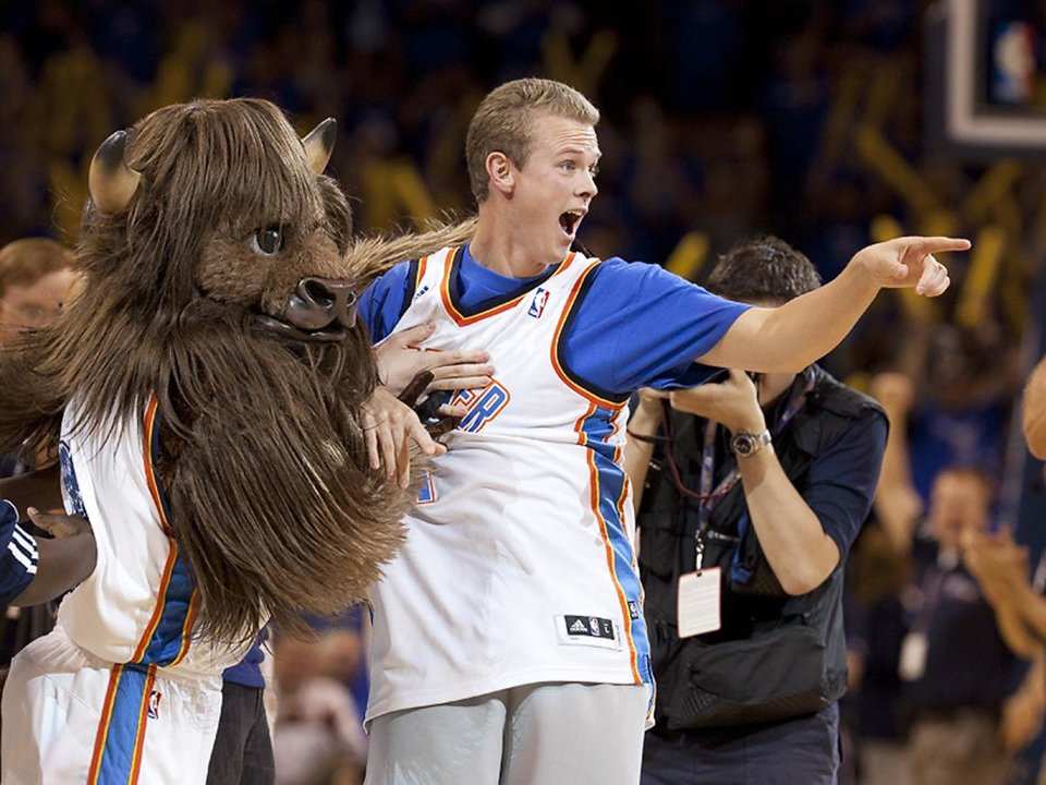 Photo - Roman Owen celebrates with Rumble the Bison after hitting a $20,000 halfcourt shot on Tuesday night.