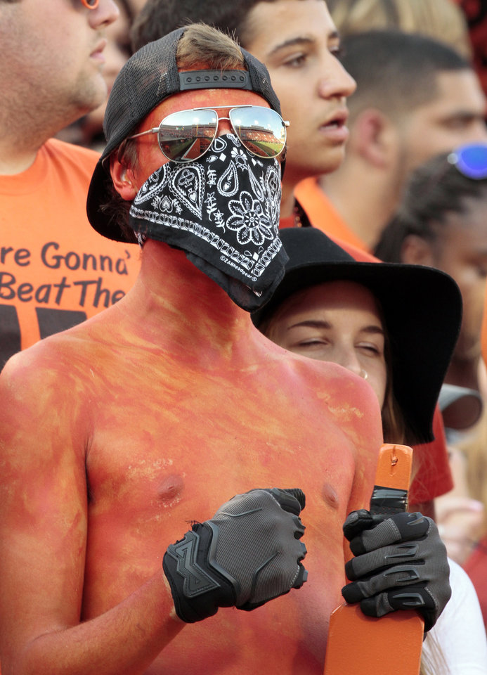 Photo - Detrick Bombarger wears his team colors in the student section before the college football game between the Oklahoma State Cowboys (OSU) and the Central Arkansas Bears at Boone Pickens Stadium in Stillwater, Okla., Saturday, Sept. 12, 2015. Photo by Steve Sisney, The Oklahoman