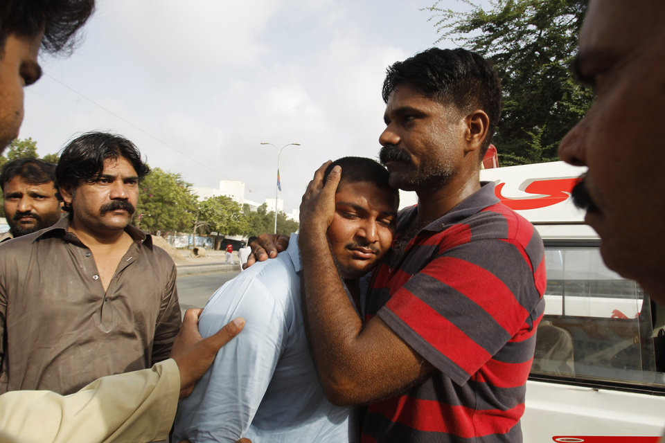 Photo - People comfort a family member of a security officer killed in late Sunday's attack at the Jinnah International Airport in Karachi, Pakistan, Monday, June 9, 2014. The Pakistani Taliban on Monday claimed responsibility for a brazen five-hour assault on the country's busiest airport that saw gunmen disguised as police guards storm the international terminal in Karachi, set off explosions and killing over a dozen of people. (AP Photo/Fareed Khan)
