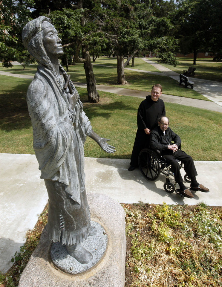 Photo - The Rev. Matthew J. Brown, O.S.B., seated, and Brother Simeon Spitz, O.S.B., look at a statue of St. Kateri Tekakwitha, the first Roman Catholic American Indian saint, that sits on the grounds of St. Gregory's Abbey in Shawnee.  PAUL HELLSTERN - Oklahoman