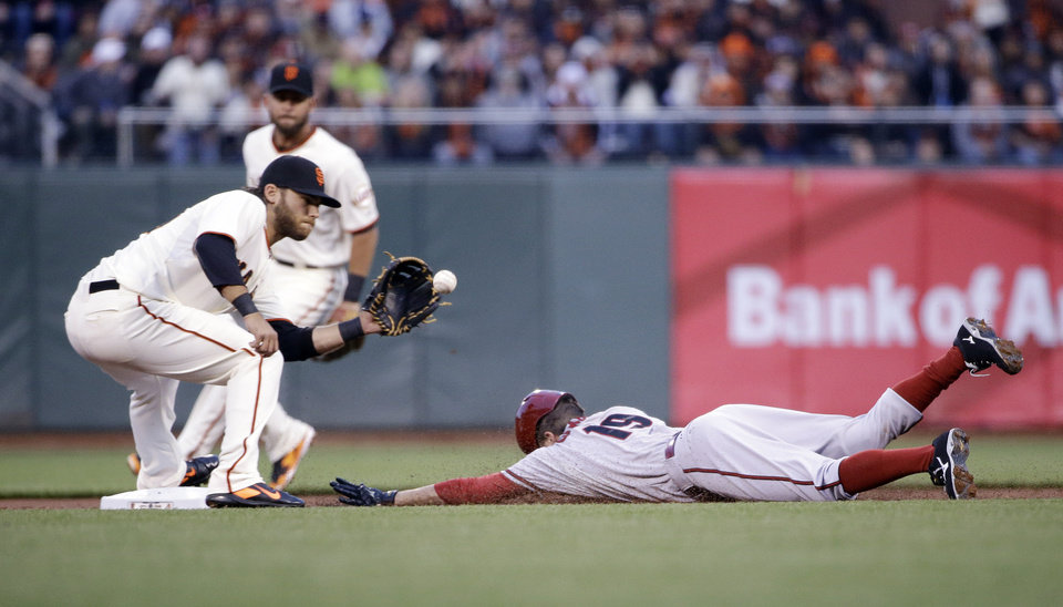 Photo - Arizona Diamondbacks' Tony Campana, right, is tagged out by San Francisco Giants shortstop Brandon Crawford, left,  while trying to steal second base during the first inning of a baseball game on Thursday, April 10, 2014, in San Francisco. (AP Photo/Marcio Jose Sanchez)