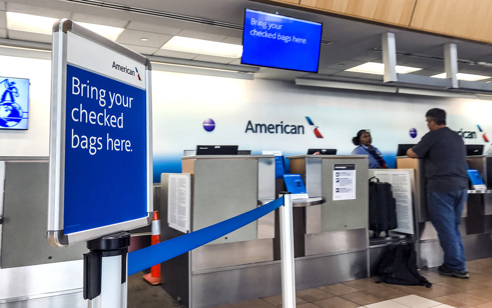 Photo - Travelers make their way through Will Rogers World Airport at the American Airlines counter in Oklahoma City, Okla. on Tuesday, June 19, 2018. The airport is offering airlines who bring in nonstop service to destinations that are currently not offered free marketing incentives.  Photo by Chris Landsberger, The Oklahoman