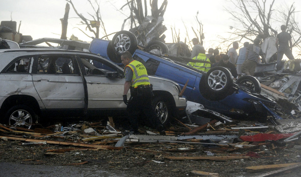 Photo - An emergency worker searches through damaged cars along Range Line Road in Joplin, Mo. in Joplin, Mo. after a tornado struck the city on Sunday evening, May 22, 2011. (AP Photo/The Joplin Globe, Roger Nomer) ORG XMIT: MOJOP107