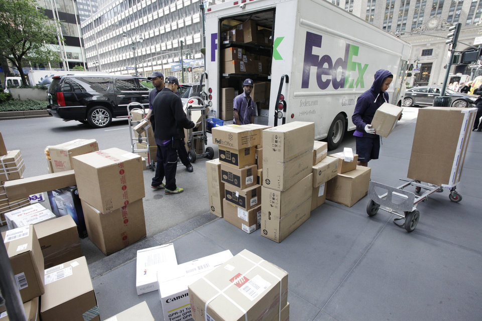 Photo -   In this Friday, May 11, 2012, file photo, FedEx workers sort boxes for delivery as they are unloaded from a FedEx truck in New York. FedEx Corp. said Tuesday, June 19, 2012, that slow global growth will crimp its earnings results over the next 12 months, but it's vowing to make significant cost cuts to make up for any shortfall.(AP Photo/Mark Lennihan)