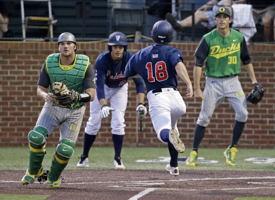 Photo - Vanderbilt's Nolan Rodgers (18) scores on a double by Dansby Swanson as Oregon catcher Shaun Chase, left, waits for the throw during the third inning of an NCAA college baseball regional tournament game Sunday, June 1, 2014, in Nashville, Tenn. Backing up the play at right is Oregon pitcher Stephen Nogosek (30). (AP Photo/Mark Humphrey)