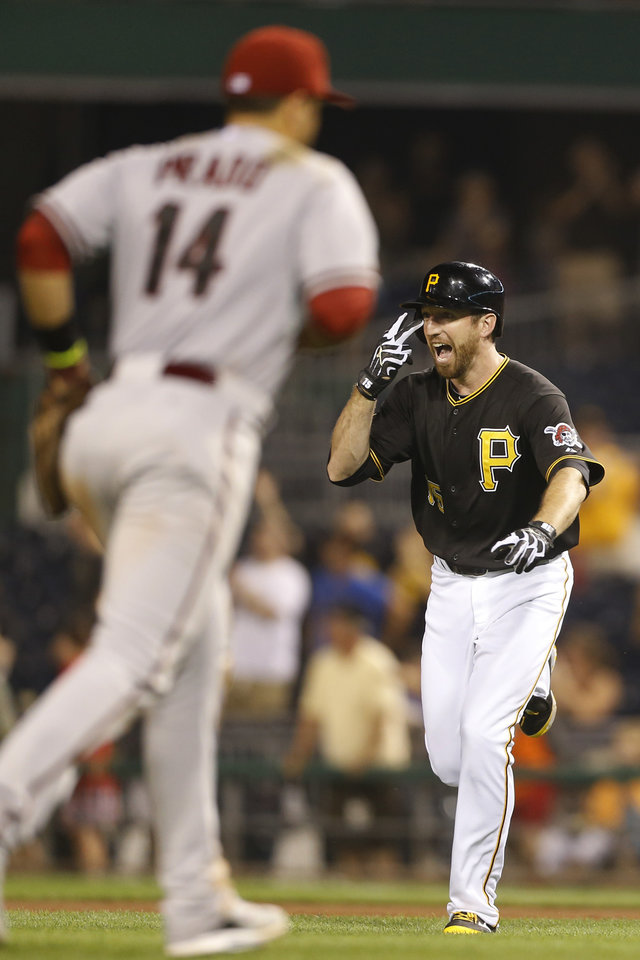 Photo - Pittsburgh Pirates' Ike Davis, right, celebrates  drivng in the game winning run as Arizona Diamondbacks third baseman Martin Prado (14) leaves the field in the ninth inning of the baseball game on Tuesday, July 1, 2014, in Pittsburgh. The Pirates scored three runs in the bottom of the ninth inning to win 3-2. (AP Photo/Keith Srakocic)