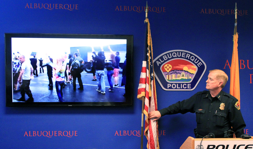 Photo - Albuquerque Police Chief Gorden Eden shows video and photographs from an hours' long protest over police shootings during a news conference in Albuquerque, N.M. on Monday, March 31, 2014. (AP Photo/Susan Montoya Bryan)