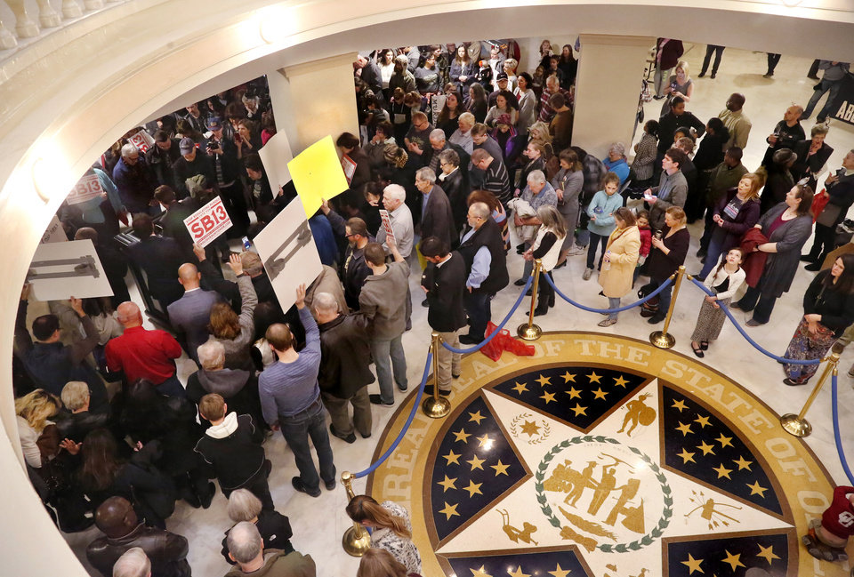 Photo -  A vocal crowd of about 400 pro-life activists carried signs condemning abortion, calling it an act of murder,  and cheered a lengthy slate of speakers who urged the group to stand and fight  for the repeal of legalized abortion in America during a rally on the first floor of the state Capitol Tuesday morning, Feb. 12, 2019. [JIM BECKEL/THE OKLAHOMAN]