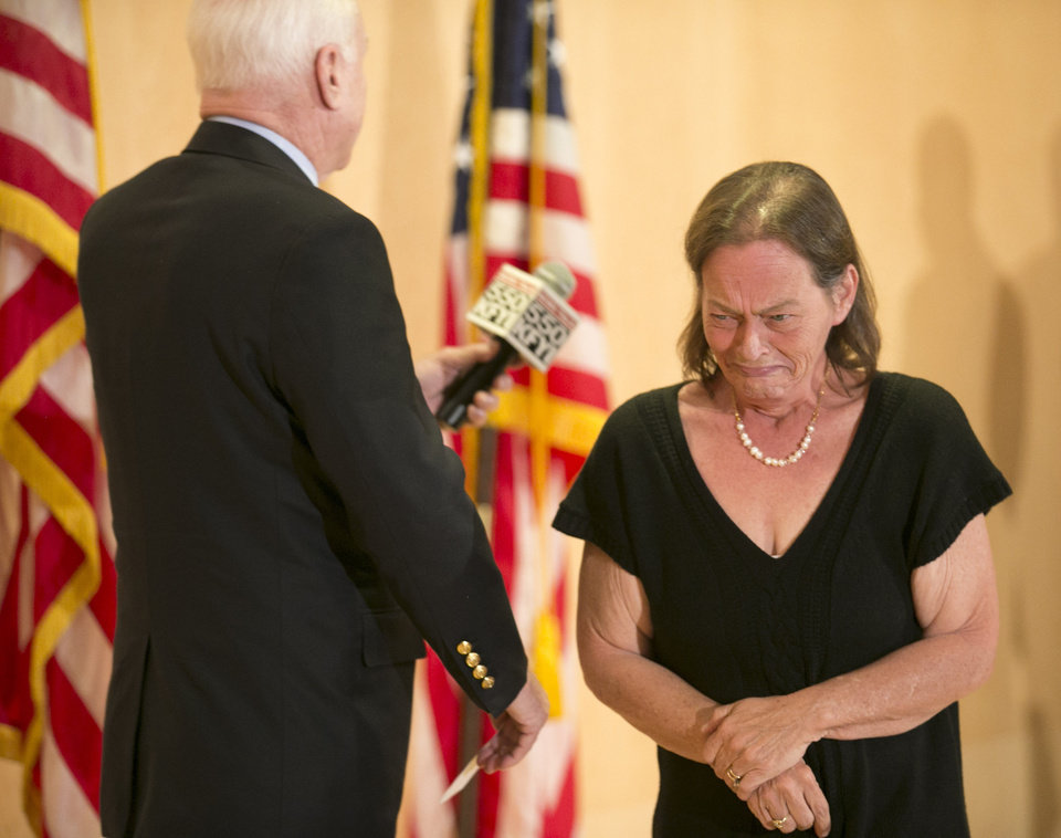 Photo - Vicky Olson of Phoenix, cries after speaking about her husband, Michael Olson, a patient of the Phoenix VA Health Care System who died in March of 2014, as U.S. Senator John McCain (R-AZ) (left) holds the mic during an open forum discussing the recent allegations of gross mismanagement and neglect at the Phoenix VA Health Care System, at the Burton Barr Central Library in Phoenix on Friday, May 9, 2014. (AP Photo/The Arizona Republic, Tom Tingle)