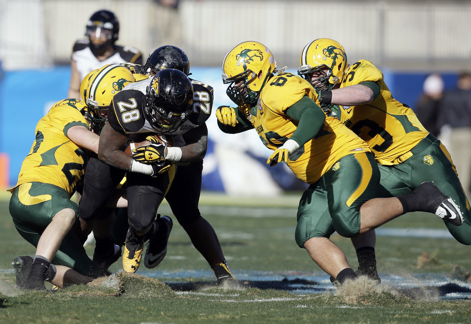 Photo - Towson running back Terrance West (28) digs up turf as North Dakota State's Colten Heagle, left, Leevon Perry (69) and Kyle Emanuel (53) combine for the stop in the second half of the FCS championship NCAA college football game, Saturday, Jan. 4, 2014, in Frisco, Texas. NDSU won 35-7. (AP Photo/Tony Gutierrez)
