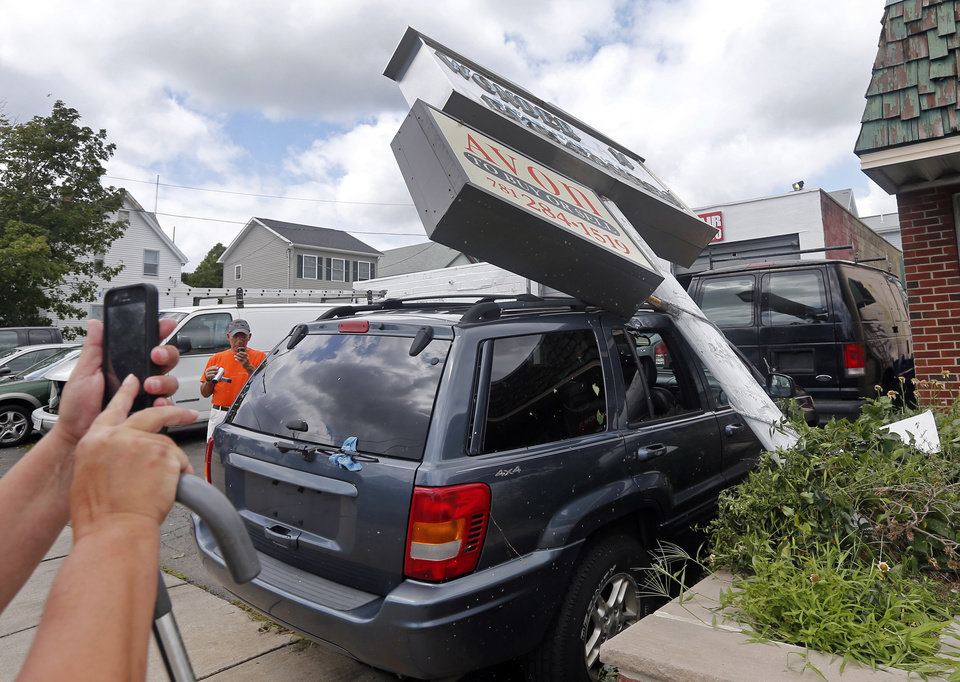 Photo - People take cellphone pictures of a large commercial sign which fell on a car in Revere, Mass., Monday, July 28, 2014 after a tornado touched down. Revere Deputy Fire Chief Mike Viviano says the fire department in that coastal city has received dozens of calls reporting partial building and roof collapses, and downed trees and power lines. Viviano says there are no immediate reports of deaths or serious injuries. (AP Photo/Elise Amendola)