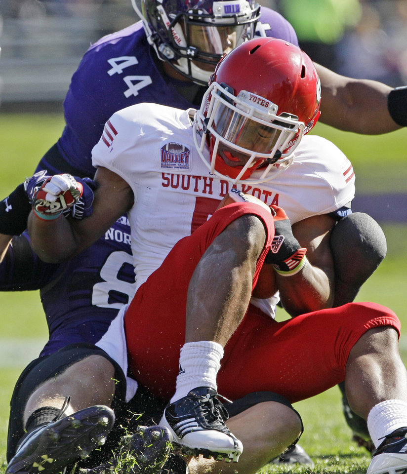 Photo -   South Dakota running back Jasper Sanders (5) is tackled by Northwestern defensive line Quentin Williams (88) during the first half of an NCAA college football game in Evanston, Ill., Saturday, Sept. 22, 2012. (AP Photo/Nam Y. Huh)