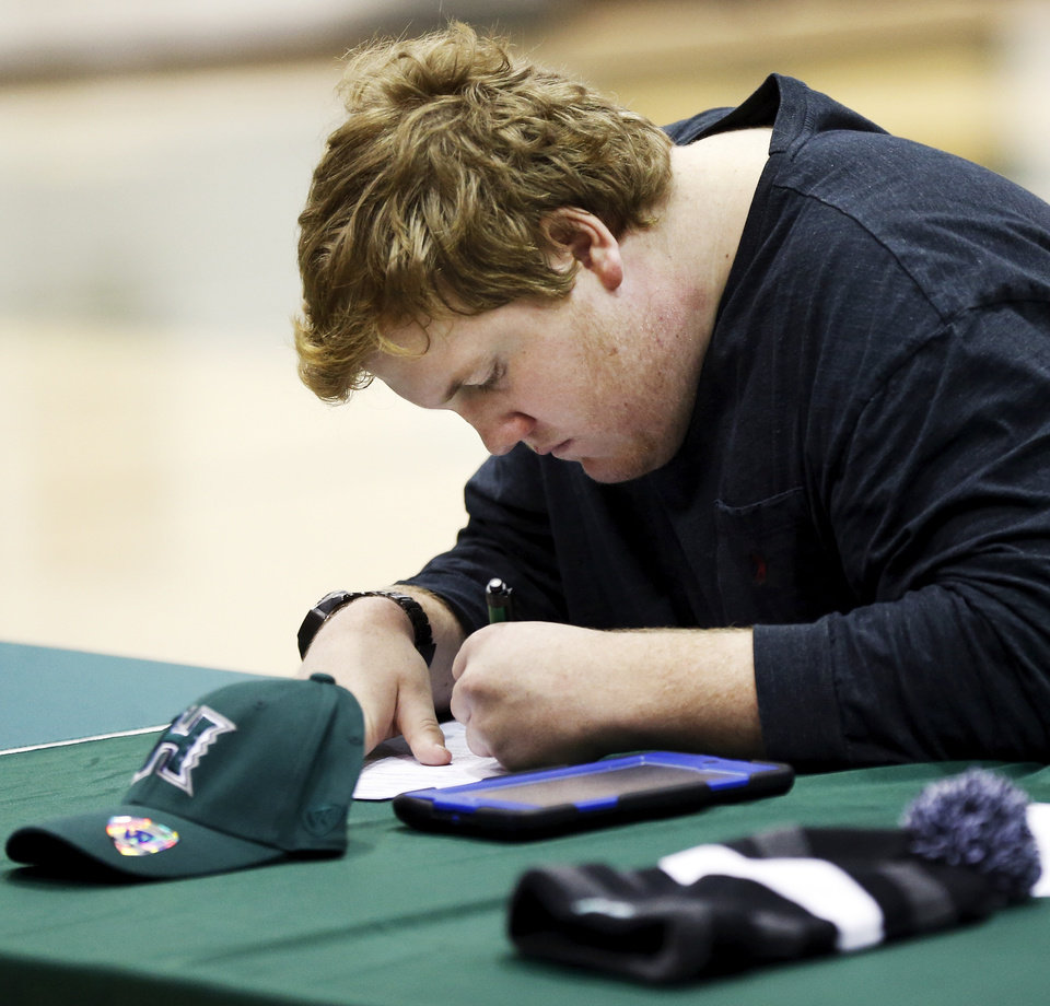 Photo - J.R. Hensley signs to play football at the University of Hawaii during a national signing day ceremony at Edmond Santa Fe High School in Edmond, Okla., Wednesday, Feb. 4, 2015. Photo by Nate Billings, The Oklahoman