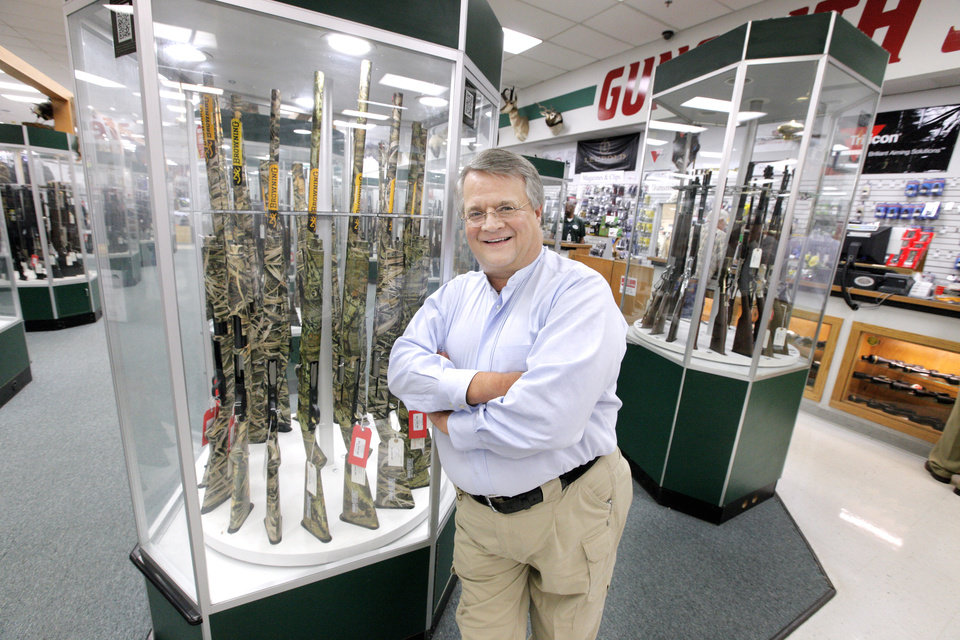 Photo -  Miles Hall, founder and president of H & H Gun Range, is shown among display cases of Browning shotguns inside H & H Gun Range, 400 S Vermont Ave.     PAUL B. SOUTHERLAND -  PAUL B. SOUTHERLAND