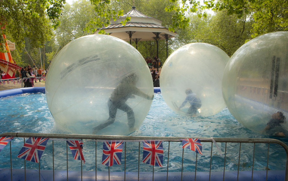 Photo - Children play in large spheres floating in a pool in Hyde Park where large screens are broadcasting the Royal Wedding in London, Friday, April, 29, 2011. (AP Photo/Joel Ryan) ORG XMIT: LENT112