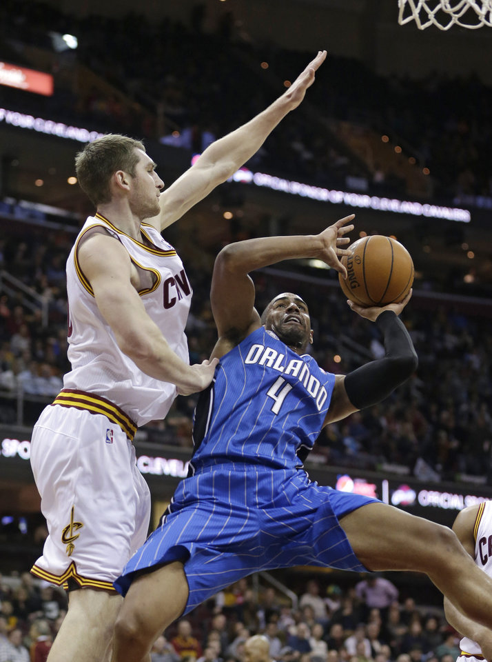 Photo - Orlando Magic's Arron Afflalo, right, shoots over Cleveland Cavaliers' Tyler Zeller during the first quarter of an NBA basketball game Wednesday, Feb. 19, 2014, in Cleveland. (AP Photo/Tony Dejak)