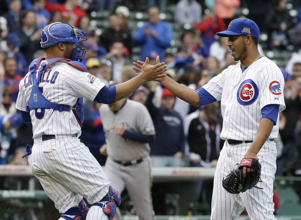 Photo - Chicago Cubs relief pitcher Hector Rondon, right, celebrates with catcher Welington Castillo after the Cubs defeated the Milwaukee Brewers 3-0 in a baseball game in Chicago, Saturday, May 17, 2014.  (AP Photo/Nam Y. Huh)