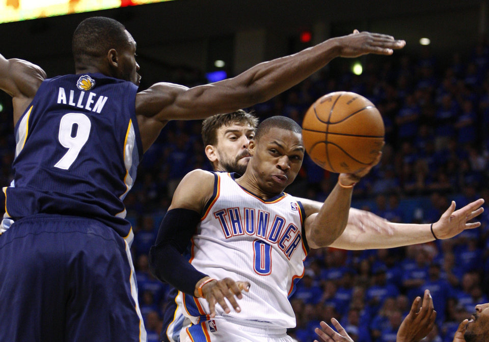 Photo - Oklahoma City Thunder guard Russell Westbrook, right, passes from under the basket between Memphis Grizzlies center Marc Gasol, center, of Spain, and guard Tony Allen, left, in the fourth quarter of Game 2 of a second-round NBA basketball playoff series in Oklahoma City, Tuesday, May 3, 2011. Oklahoma City won 111-102. (AP Photo/Alonzo Adams)