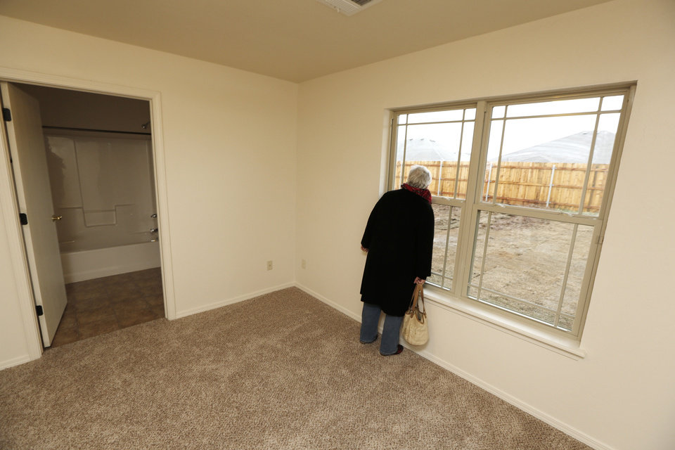 Fran Mutz looks out a window of Lisa Sumner's new Central Oklahoma Habitat for Humanity home in Yukon at a dedication Wednesday. It was the charity homebuilder's 700th home since its start in 1986. <strong>Steve Gooch - The Oklahoman</strong>