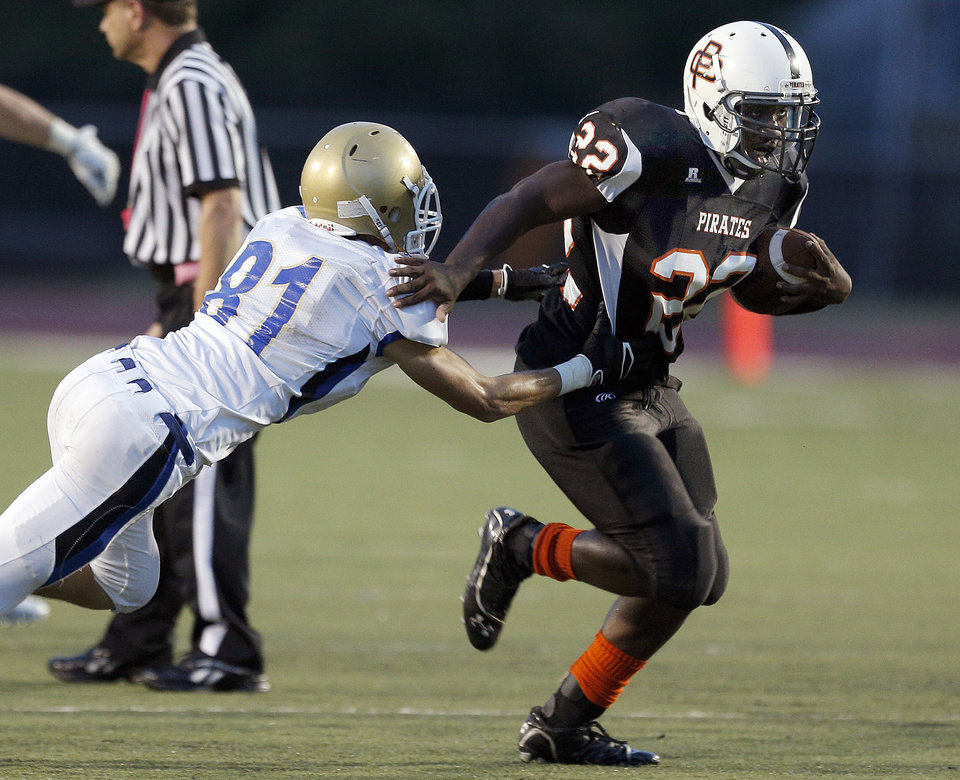 Putnam City's Denzel Dean slips past Choctaw's Ty Stayton during the high school football game between Putnam City and Choctaw at Putnam City High School in Oklahoma City, Thursday, Sept. 19, 2013. Photo by Sarah Phipps, The Oklahoman