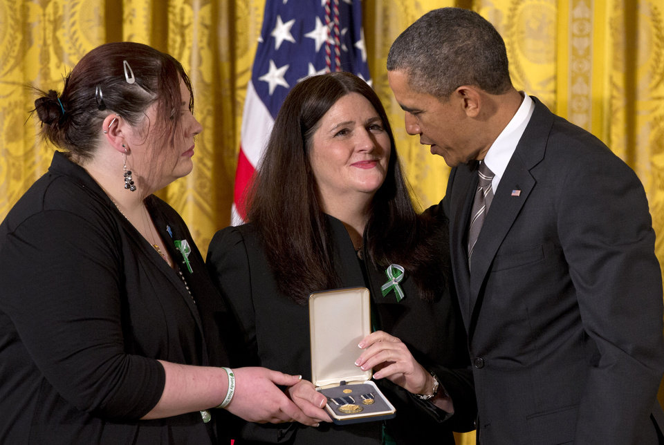 President Barack Obama presents a 2012 Citizens Medal to the family of slain Sandy Hook Elementary School teacher's aide Rachel Davino, mother Mary Davino, center, and sister, Sarah Davino, Friday, Feb. 15, 2013, in the East Room of the White House in Washington.  (AP Photo/Jacquelyn Martin)