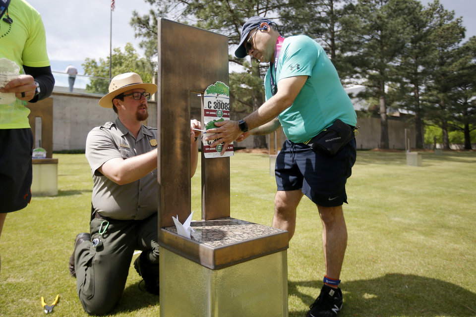 Photo - National Park Park Ranger Ian Harvey helps relay runner Steve Romero place running bibs on the chair of Paul Gregory Beatty Broxterman after Romero ran with the Ag Boyz relay team in the Oklahoma City Memorial Marathon in Oklahoma City, Sunday, April 28, 2019. [Bryan Terry/The Oklahoman]