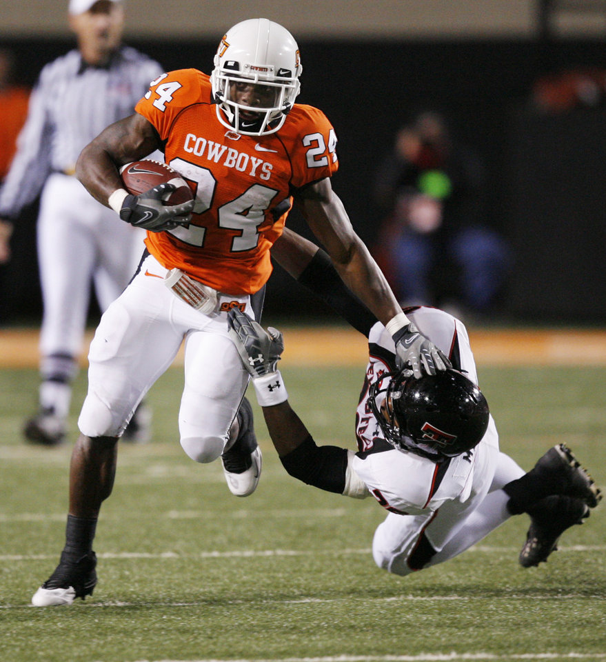 Photo - OSU's Kendall Hunter (24) breaks away from Franklin Mitchem (26) of Texas Tech on a carry in the third quarter during the college football game between Oklahoma State University (OSU) and Texas Tech University at Boone Pickens Stadium in Stillwater, Okla. Saturday, Nov. 14, 2009. OSU won, 24-17. Photo by Nate Billings, The Oklahoman