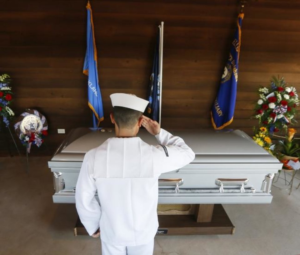 Photo -  A Navy sailor salutes the casket of Herman White during the funeral service for the World War II veteran at Grace Hill Cemetery in Perry, Okla., Wednesday, Sept. 4, 2019. Hundreds of people attended Navy Seaman 2nd Class White's funeral after learning that he had no surviving family members to be there. [Nate Billings/The Oklahoman]