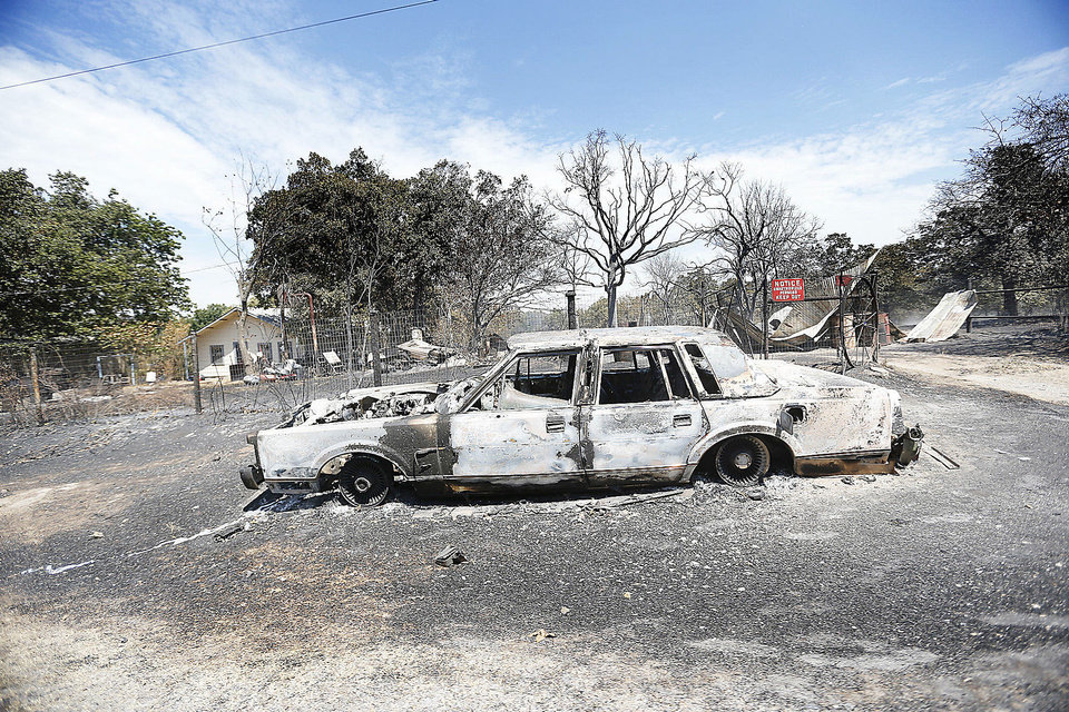 Photo - A car is pictured burned , Sunday, Aug. 5, 2012, in the community Oak Grove near Drumright, Okla., after wildfires moved through the area Saturday. Photo by Sarah Phipps, The Oklahoman