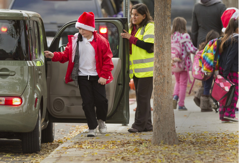 Photo - Volunteer parents welcome school children arriving at the Theodore Roosevelt School in Burbank, Calif., early Monday, Dec. 17, 2012. Teachers, parents and students are making an anxious return to school this week after a gunman stormed into Sandy Hook Elementary School in Newtown, Conn., on Friday, shooting to death 26 people before killing himself. (AP Photo/Damian Dovarganes)