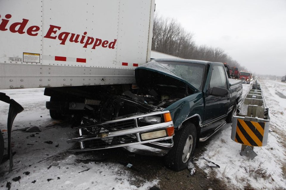 A truck is pinned under a trailer on Southbound 23 in Grand Blanc, Mich., which closed for almost three hours after a 33-vehicle wreck Thursday, Jan. 31, 2013. (AP Photo/The Grand Rapids Press, Sammy Jo Hester)