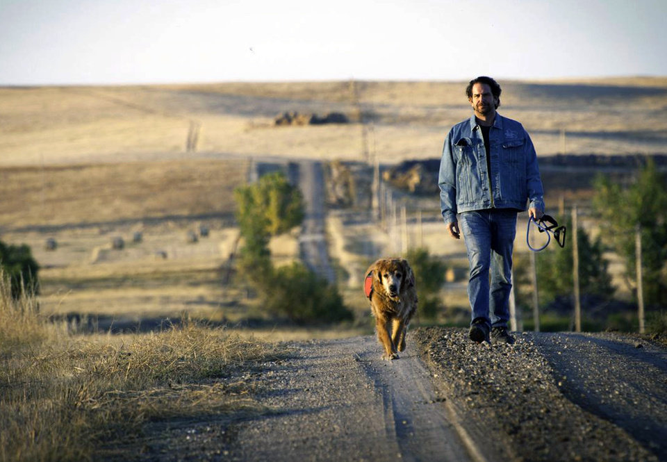 Photo - In this Oct. 2011 photo provided by Explore.org, philanthropist Charlie Annenberg, with his golden retriever, Lucky, take a walk during a visit with the medicine men and people of the Lakota Nation in Pine Ridge, S.D. For 16 years,  Lucky has been his sidekick, soul mate and inspiration.  In 2010, Annenberg started Dog Bless You, a journal of their travels as told by Lucky but written by Annenberg. (AP Photo/Explore.org)
