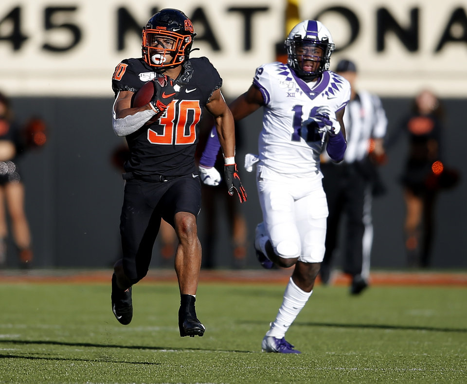 Photo - Oklahoma State's Chuba Hubbard (30) rushes for a 92-yard touchdown as TCU's Jeff Gladney (12) chases him in the third quarter during the college football game between the Oklahoma State University Cowboys and the TCU Horned Frogs at Boone Pickens Stadium in Stillwater, Okla.,  Saturday, Nov. 2, 2019. OSU won 34-27. [Sarah Phipps/The Oklahoman]