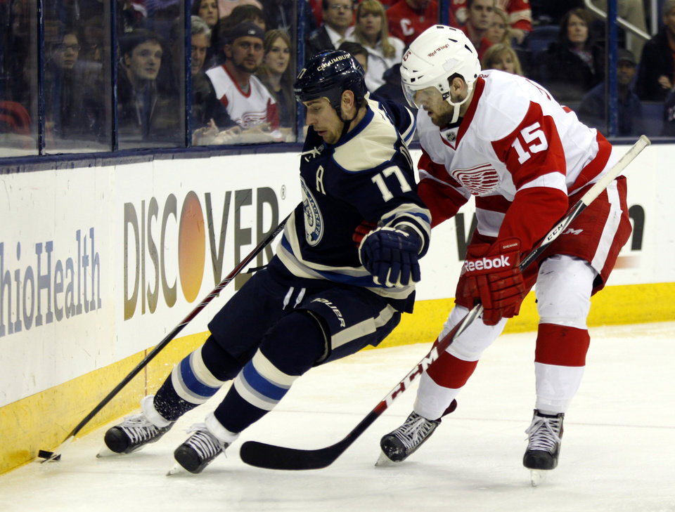 Photo - Columbus Blue Jackets' Brandon Dubinsky, left, works for the puck against Detroit Red Wings' Riley Sheahan in the second period of an NHL hockey game in Columbus, Ohio, Tuesday, March 25, 2014. (AP Photo/Paul Vernon)