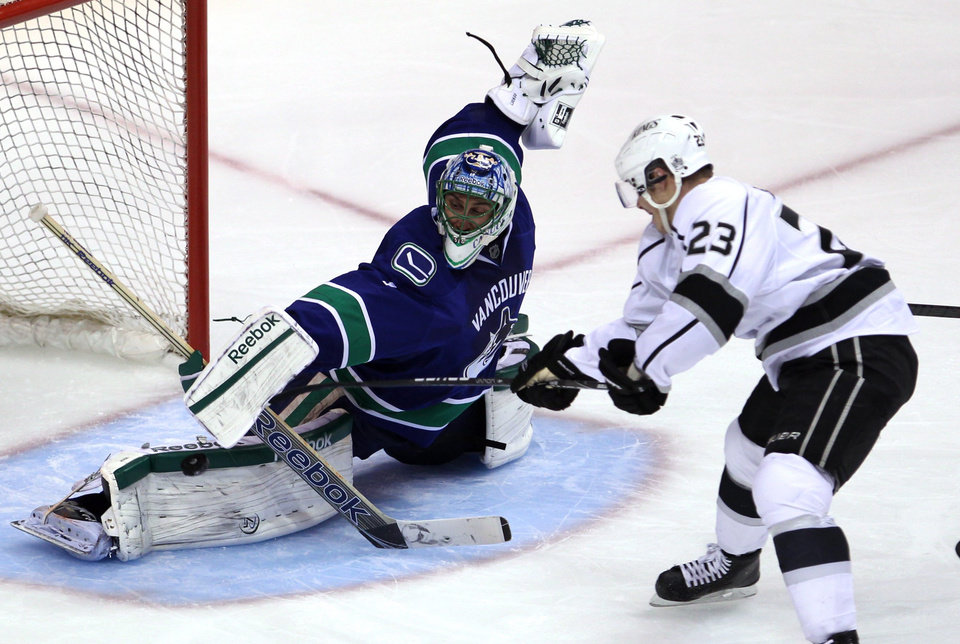 Los Angeles Kings right wing Dustin Brown (23) sends a shot past Vancouver Canucks goalie Roberto Luongo (1) during the second period of Game 2 of a first-round NHL hockey Stanley Cup playoff series in Vancouver, British Columbia, Friday, April, 13, 2012. (AP Photo/The Canadian Press, Jonathan Hayward)