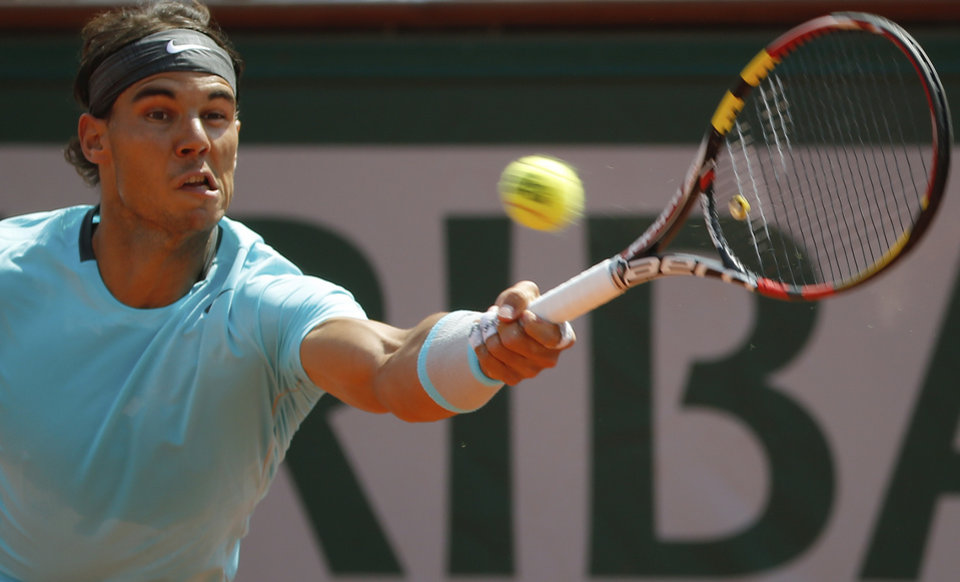Photo - Spain's Rafael Nadal returns the ball during the final of the French Open tennis tournament against Serbia's Novak Djokovic at the Roland Garros stadium, in Paris, France, Sunday, June 8, 2014.  (AP Photo/Michel Euler)