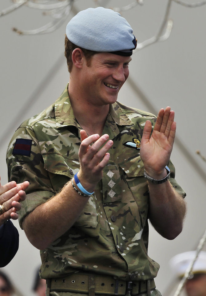 Photo - Britain's Prince Harry applauds during the opening ceremony for the 2013 Warrior Games, at the U.S. Olympic Training Center, in Colorado Springs, Colo., Saturday May 11, 2013. (AP Photo/Brennan Linsley)