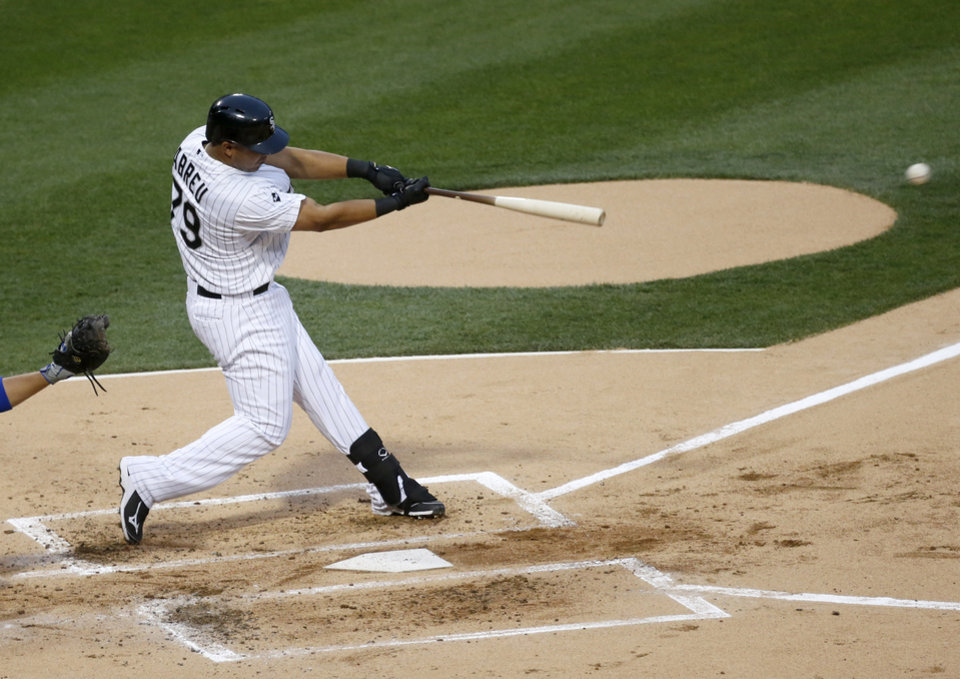 Photo - Chicago White Sox's Jose Abreu hits a single off Chicago Cubs starting pitcher Jake Arrieta during the first inning of an interleague baseball game Thursday, May 8, 2014, in Chicago. (AP Photo/Charles Rex Arbogast)