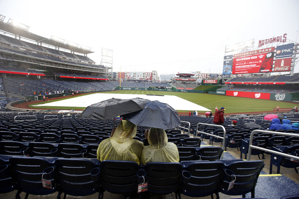 Photo - Fans sit under umbrellas in the rain before an exhibition baseball game between the Washington Nationals and the Detroit Tigers at Nationals Park Saturday, March 29, 2014, in Washington. The game was canceled due to weather. (AP Photo/Alex Brandon)